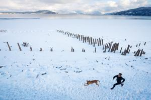 Noelle Zmuda And Her Dog Tink Go For A Cold Winter Run On Pond Oreille Bay Trail, Sandpoint, Idaho by Ben Herndon