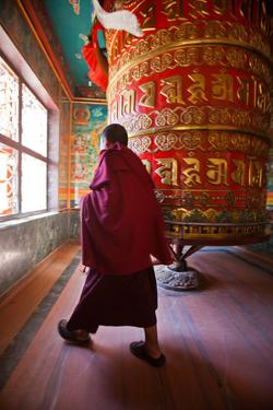 A Monk Spins the Worlds Largest Prayer Wheel Near Boudhanath Stupa by Ben Horton