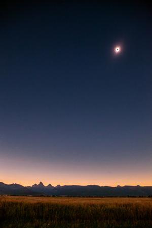 A total solar eclipse over the Teton mountains and farm land. by Ben Horton