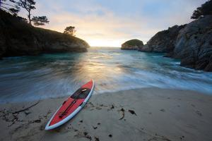 A Wave Washes Up China Cove at Sunset to a Stand Up Paddle Board by Ben Horton