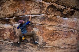A Woman Climbs Gunsmoke V3 in Joshua Tree National Park by Ben Horton