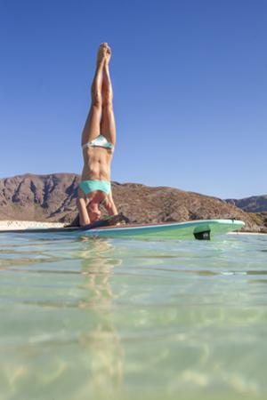 A woman doing paddleboard yoga in the shallow waters of Ballandra Bay. by Ben Horton