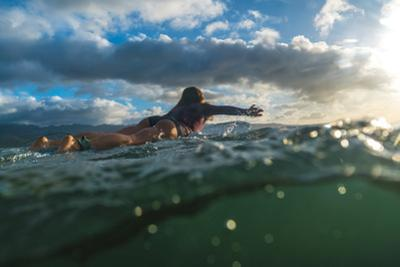 A woman surfing on the North Shore of Hawaii. by Ben Horton