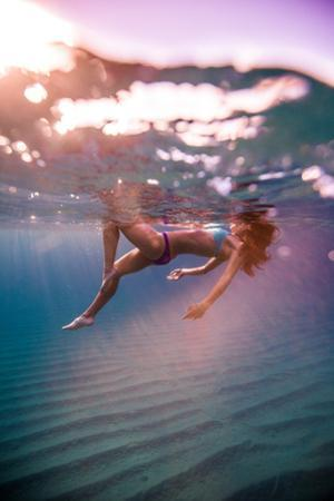 A woman swimming in the clear waters of Baja. by Ben Horton