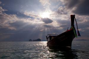 Andaman Sea: A Man Leans Off of a Long Tail Boat in the Andaman Sea under Rays of Light by Ben Horton