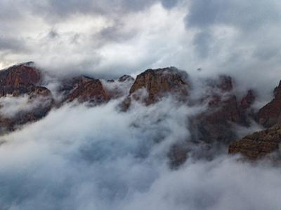 As the clouds break, Kolob canyons rock walls become visible. by Ben Horton