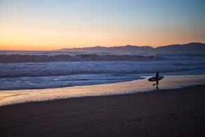 El Porto Beach, Los Angeles, California, USA: A Surfer Exits the Waves at Dusk by Ben Horton