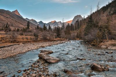 High alpine peaks at sunset over a mountain stream. by Ben Horton