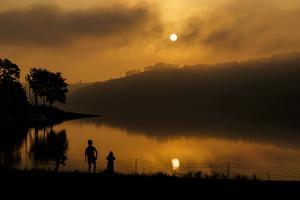Germany, North Rhine-Westphalia, Playing Children on the Lake in Front of the Morning Sun by Benjamin Engler