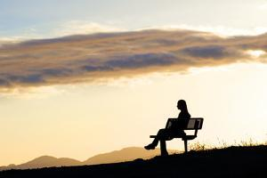 A Woman in Silhouette Sits on a Bench Along the Shelf Road Trail in Ojai California by Bennett Barthelemy