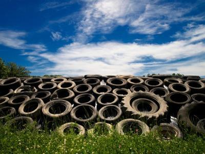 Heap of Old Tyres on Grass, under Blue Sky