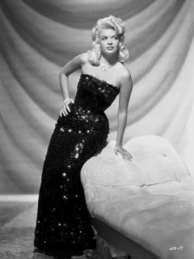 Jayne Mansfield Posed and sitting on the Couch in Black Sequin Silk Shoulder Dress by Bert Six