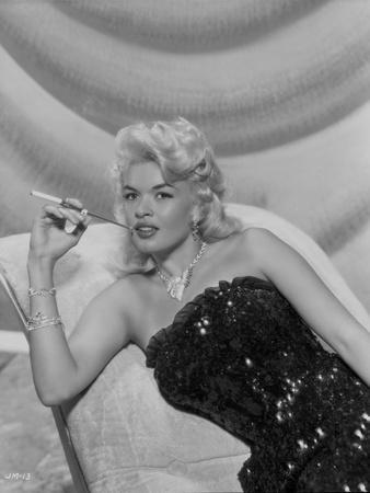 Jayne Mansfield sitting on the White Silk Couch in Black Sequin Strapless Dress and Pearl Necklace