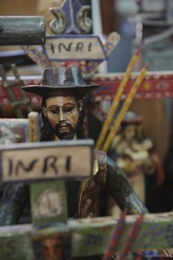 A Carved Wooden Figure Surrounded by Crosses and Other Antiques in a Shop by Beth Wald