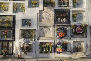 A Nun Cleans the Grave Niche of a Relative in the Wall of Graves, Cementerio De Cayma by Beth Wald