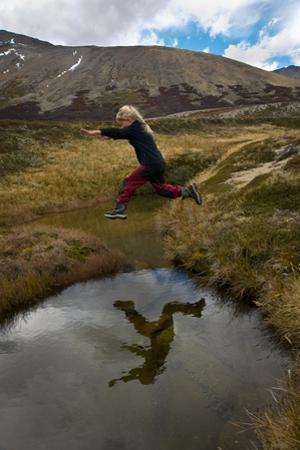 A Young Girl Leaps Over a Stream During a Trek by Beth Wald