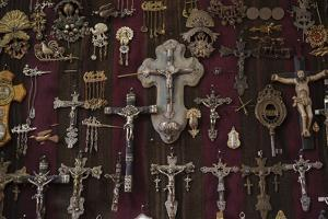 Crosses, Jewelry and Other Old Items Hang on a Wall in an Antique Shop by Beth Wald