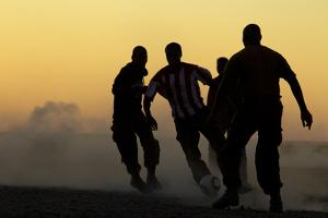 Silhouetted Men Playing Soccer at Sunset by Beverly Joubert