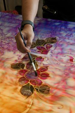 Batik artist painting silk in factory of Kuala Lumpur, Malaysia. by Bill Bachmann
