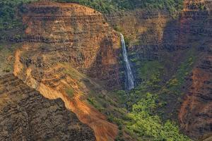 Kauai, Hawaii. Waimea Canyon State Park red cliffs from above canyon with waterfall by Bill Bachmann