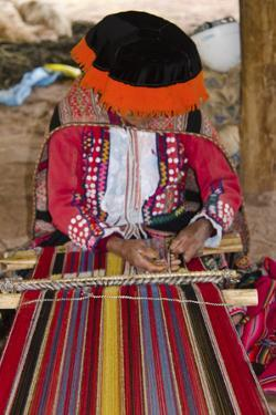 Local woman in the Sacred Valley Peru weaving with yarn in traditional clothes by Bill Bachmann