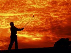 Man Swinging Golf Club at Sunset by Bill Bachmann