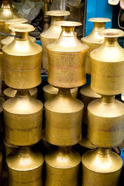 Stack of beautiful brass milk jugs or pots in Durbar Square in center of village of Kathmandu Nepal by Bill Bachmann