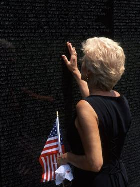 Woman at Vietnam Memorial, Washington D.C., USA by Bill Bachmann