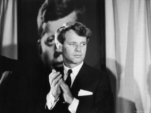 Robert F. Kennedy Campaigning in Front of Poster Portrait of His Brother President John F. Kennedy by Bill Eppridge