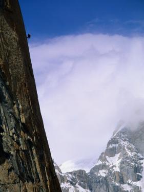 A Climber Rappels Down a Sheer Granite Face Before an Approaching Storm by Bill Hatcher