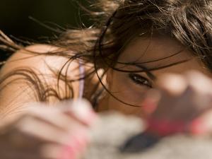 A Woman Rock Climber Eyes Her Next Hand Hold as She Climbs a Rock Face by Bill Hatcher