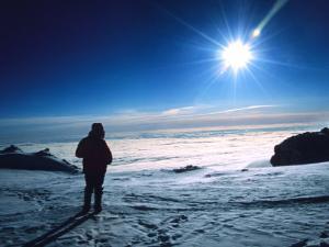 Climber Watches the Midnight Sun Set from High Camp on Denali, Alaska by Bill Hatcher