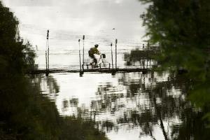 Reflection of a Mountain Biker on a Munda Biddi Trail Suspension Bridge, Collie River, Australia by Bill Hatcher