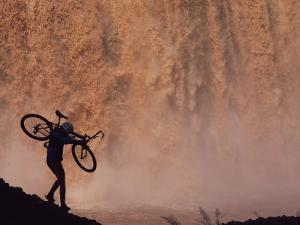 Silhouetted Cyclist Carrying Cycle Past Falls by Bill Hatcher