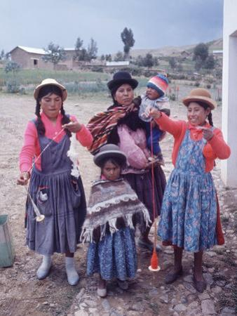 Mother and Four Children Wearing Derby Hats, Playing with Ball of Yarn, Andean Highlands of Bolivia by Bill Ray