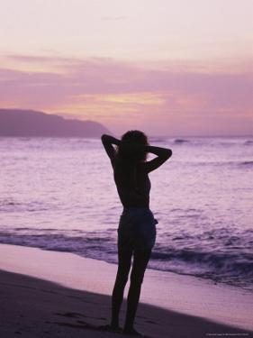 Woman Standing on Beach in Silhouette by Bill Romerhaus