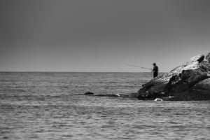 Black and White shot of a lone fisherman on rocks at the beach