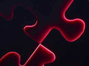 Black Puzzle with Red Light Shining Through the Cracks