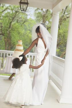 African American Bride Dancing with Flower Girl by Blend Images
