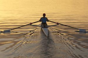 Person Rowing Sculling Boat on River by Blend Images/Pete Saloutos