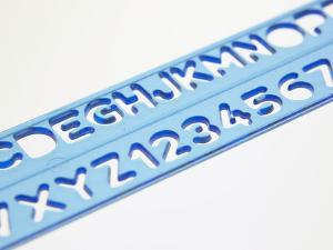 Blue Ruler Against White Background with Tracing of Alphabet and Numbers