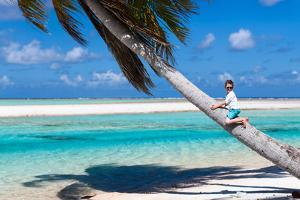 Little Boy Sitting on a Palm at Exotic Beach by BlueOrange Studio