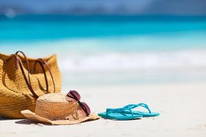 Straw Hat, Bag, Sun Glasses and Flip Flops on a Tropical Beach by BlueOrange Studio