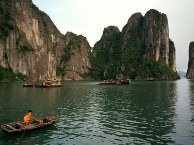 Boats Move Among the Craggy Islands of Halong Bay