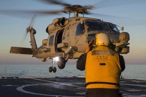 Boatswain's Mate Guides an Mh-60R Sea Hawk onto the Flight Deck