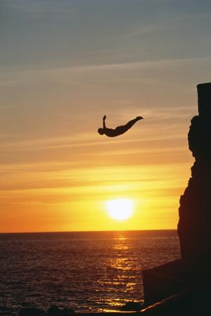 Cliff Diver above Setting Sun by Bob Krist