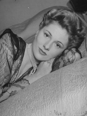 Actress Joan Fontaine Wearing Sheer Negligee While Lounging on Bed at Home by Bob Landry