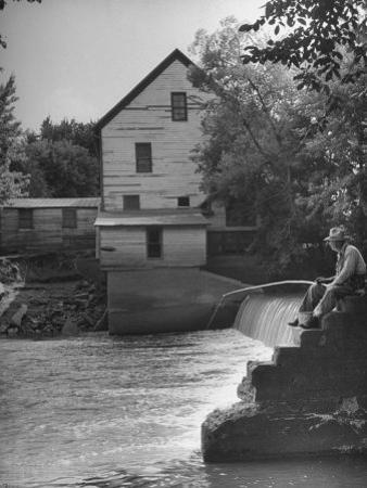 Man Fishing Beside a Waterfall and a 100 Year Old Mill by Bob Landry