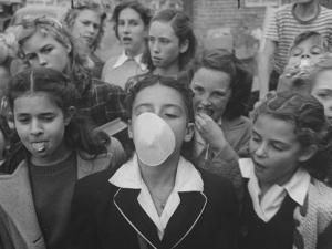 Young Girl Blowing a Bubble with Her Friends Watching by Bob Landry
