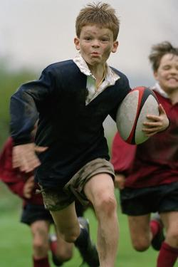 Boy Running with Rugby Ball by Bob Thomas